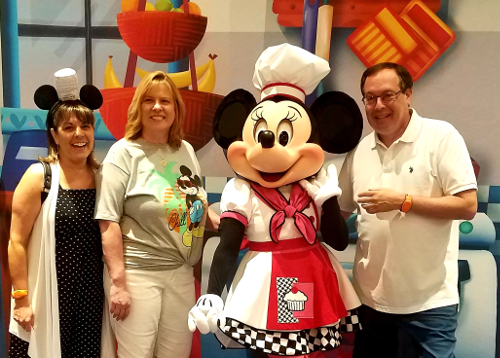 Howard, Kelly, and Patty standing with Chef Minnie Mouse at the Epcot International Food & Wine Festival
