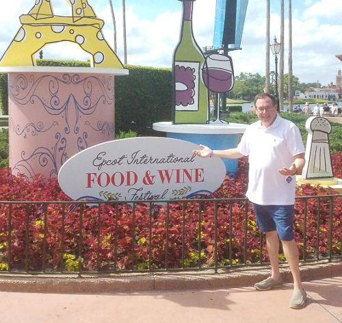 Howard standing in front of the Epcot International Food & Wine sign in Disney World, Florida
